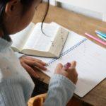 机に向かって勉強する写真